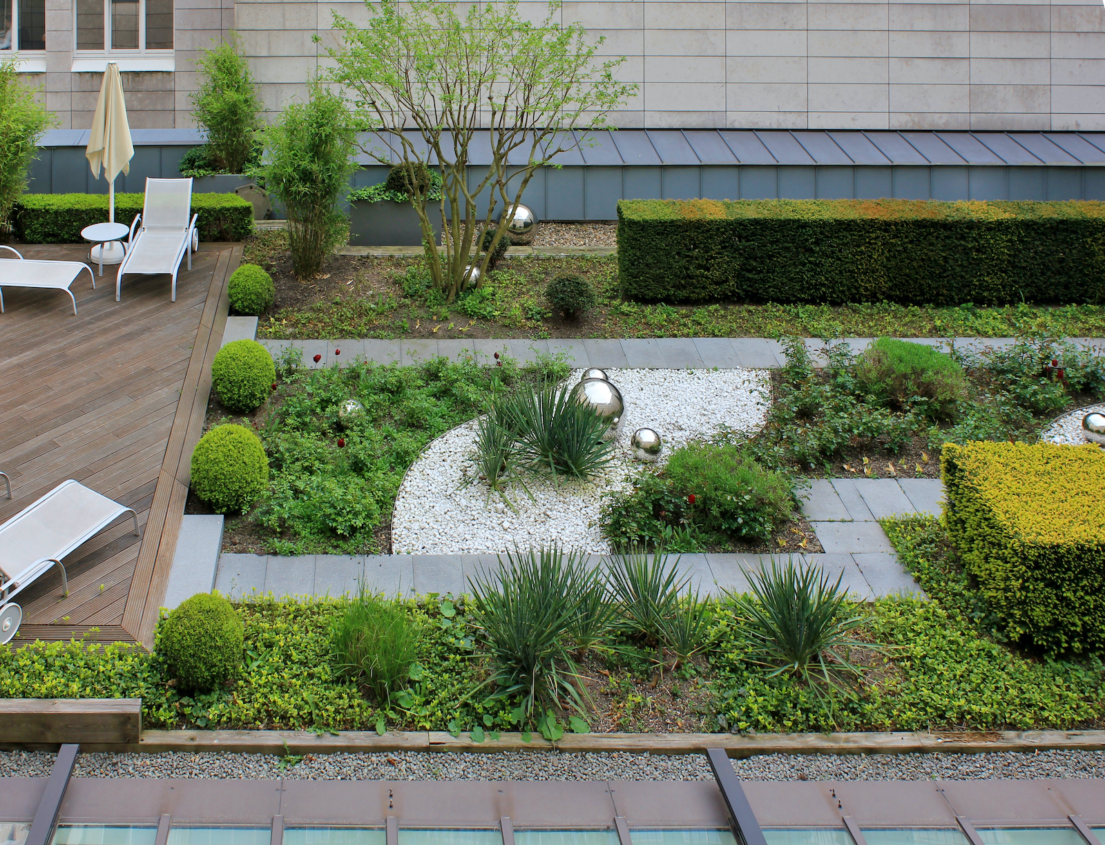 Roof garden with green plants and silver which balls and wooden terrace with rest chairs